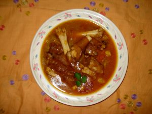 paya curry in a white bowl